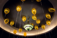 Balloons at ceiling. Gold balloons on the ceiling with lamp in the middle Royalty Free Stock Photos
