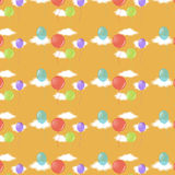Balloons and clouds. Seamless pattern with balloons and clouds on a yellow-orange background Royalty Free Stock Photography