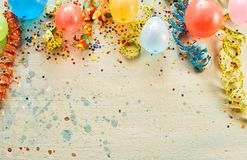Balloons, confetti, ribbons with copy space. Carnival concept of balloons, confetti, ribbons against plain background with copy space stock photos