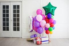 Balloons of different colors with gifts for the holiday in a room. Balloons of different colors with gifts for the holiday in a white room stock photos
