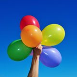 Balloons of different colors. Someone holding a bunch of balloons of different colors over the blue sky Stock Photos