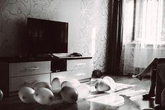 Balloons on the floor of the room and legs of a girl sitting on the sofa. Black and white image royalty free stock images