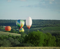 Balloons fly over the green fields, hills  summer Stock Photography