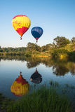 Balloons fly over the lake Stock Photo