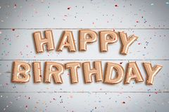 Balloons forming the words `Happy Birthday`. On wooden background Stock Photos