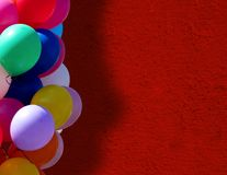 Balloons near red wall royalty free stock photography