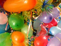 Balloons & Olives. Shot of a pair of martini glasses, one of them filled up with olives; all this is set up over a mirror. Curly ribbons and balloons give the stock images