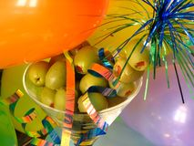 Balloons & Olives. Shot of a martini glass filled up with some olives. Curly ribbons and balloons give the picture a party/celebration felling royalty free stock photo