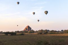Balloons over Bagan at sunrise with horses. This photo was taken Bagan, Myanmar. Bagan sunrises are truly iconic. Temples as far as the eye can see, a morning Royalty Free Stock Image