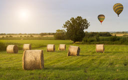 Balloons over the field. With bales Royalty Free Stock Images