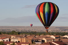 Balloons over the rooftops. Hot air balloons come close over the rooftops of houses in Albuquerque, New Mexico during the annual balloon fiesta Royalty Free Stock Image