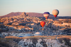 Balloons over Uchisar castle in Cappadocia Stock Photos