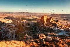 Balloons over Uchisar town in Cappadocia. Stock Image