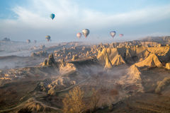 Balloons over a valley hit by beams of the sunrise Stock Image