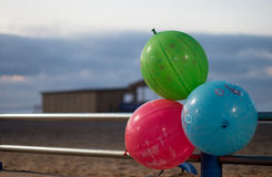 Balloons railing. Coloured balloons on a beachside railing Stock Photos