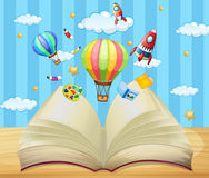 Balloons and rockets flying out of book Royalty Free Stock Photography