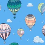 Balloons seamless  pattern on blue background. Many differently colored striped air balloons flying in the clouded sky. Clouds and birds soaring in the sky stock illustration