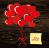 Balloons in the shape of heart bandaged with ribbon and bow, for. A holiday and birthday and a party. Red inflatable balls. Invitation.  Empty Yellow sheet of Royalty Free Stock Photography