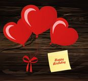 Balloons in the shape of heart bandaged with ribbon and bow, for. A holiday and birthday and a party. Red inflatable balls. Invitation.  Empty Yellow sheet of Royalty Free Stock Image