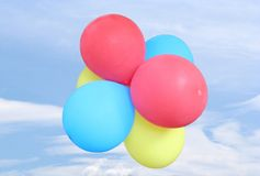 Balloons in the Sky. A group of balloons floating in a blue sky with some clouds Royalty Free Stock Images