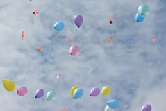 Balloons In the Sky. Colorful balloons rise against a beautiful wispy summer clouds in background Stock Image
