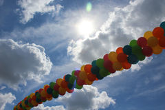 Balloons in the Sky. Multicolored balloons below the sun, clouds, and blue sky Royalty Free Stock Photography