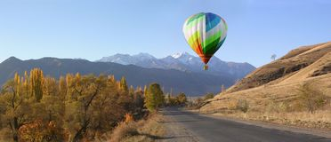 Balloons start fly on forest, hills in autumn Royalty Free Stock Photos