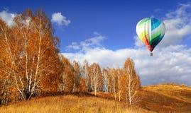 Balloons start fly on forest, hills in autumn.  stock photo