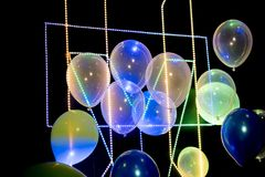 Balloons with strip led light on black background. Balloons with strip led light on black party background royalty free stock image