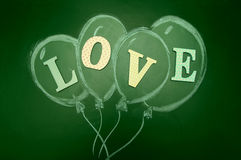 Balloons with the text of LOVE it is drawn with chalk on a blackboard. Royalty Free Stock Image