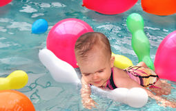 Balloons, Water and Fun. Happy baby floating in the swimming pool surrounded by balloons Stock Photos