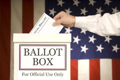 Ballot Box With Hand Voting. Male hand putting ballot in the ballot box.   American Flag background Stock Photography