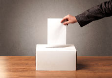 Ballot box with person casting vote. On blank voting slip, grungy background Stock Photos