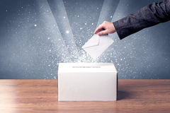 Ballot box with person casting vote. On sparkling background Stock Photo