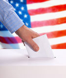 Ballot voting. A ballot is cast with the american flag in background Royalty Free Stock Image