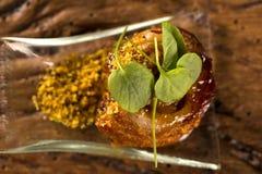 Ballotine del cerdo con pururuca, la harina del agua, el puré de la calabaza y los brotes en una cuchara Imagen de archivo libre de regalías