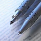 Ballpen tips. Studio shot of 2 ballpen tips in blue ambiance over book page Royalty Free Stock Image