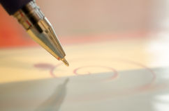 Ballpoint. Pen with gold tip, on a pink background. Closeup Stock Image