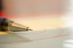 Ballpoint. Pen with gold tip, on a pink background. Closeup Stock Images