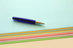 Ballpoint  and colored papers. Blue ballpoint  lying on a stack of colored papers Stock Image