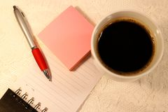 A ballpoint ink pen and pink sticky notes lies on a lined page from a spiral notebook. And a cup of coffee on the side. royalty free stock photography
