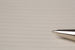 Ballpoint pen on blank lined paper. Close up of the nib of a silver metal ballpoint pen on blank lined paper with copyspace for your text Royalty Free Stock Photo