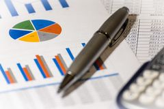 Ballpoint pen, calculator and financial charts. financial reports stock photo