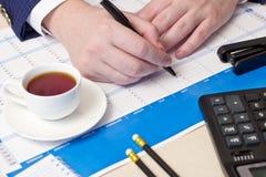 Ballpoint pen, calculator, hand Stock Image