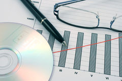 Ballpoint pen, cd and glasses on earning graphs Stock Photo