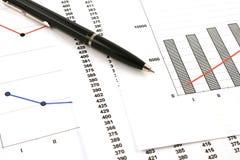 Ballpoint pen on earning graphs Stock Photos