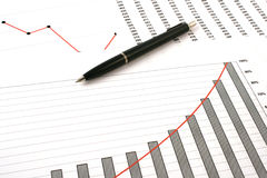 Ballpoint pen on earning graphs Royalty Free Stock Image