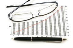 Ballpoint pen and glasses on earning graphs Stock Photography