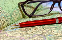 Ballpoint pen and glasses lie on geographical atlas Stock Images