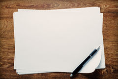 Ballpoint pen lying on sheets of paper. Ballpoint pen lying on sheets of blank white paper with copyspace for your handwriting or text, overhead view on a wooden Royalty Free Stock Photos